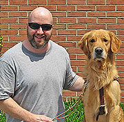 Mark Callaghan standing next to his Seeing Eye dog, a golden retriever named Javon.
