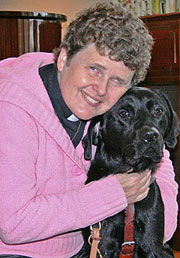 The Rev. Dr. Sharon Ballantyne hugging her Seeing Eye dog, a black Labrador retriever named Wilson.